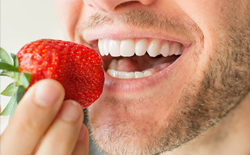 Man biting into a strawberry