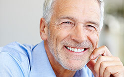Columbia Dental Implants elderly man in blue shirt smiling