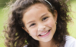 Columbia Children's Dentistry Girl with headband smiling outside
