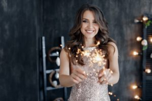 Woman with beautiful smile holding sparklers.