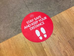 "red sticker on floor that reads, ""stay safe and keep your distance"""