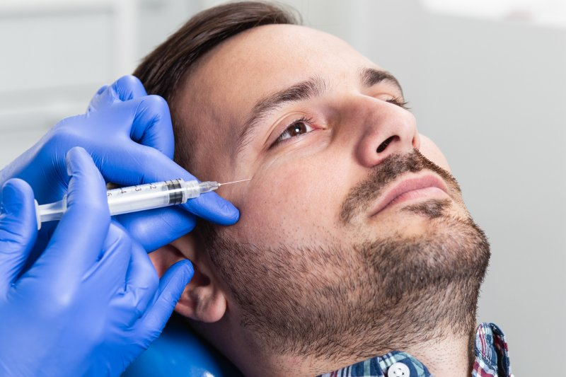 a young man having Botox injected during a session to eliminate crow's feet