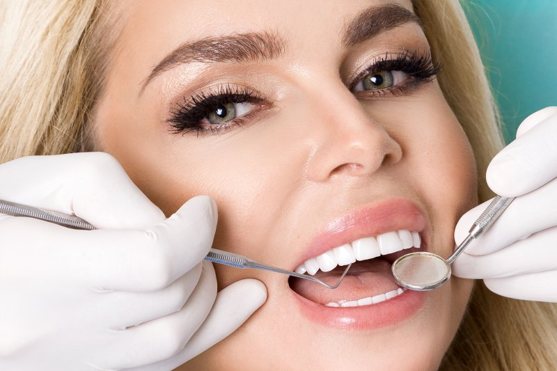 woman smiling while dentist inspects her porcelain veneers
